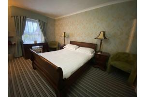 A bed or beds in a room at OYO Lamphey Hall Hotel