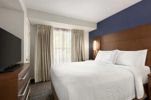 A bed or beds in a room at Residence Inn Sacramento Folsom