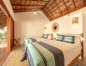 A bed or beds in a room at Mimosa Tulum