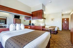 A bed or beds in a room at Trident Inn & Suites Baton Rouge