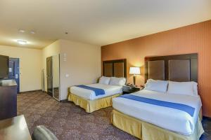 A bed or beds in a room at Holiday Inn Express Hotel & Suites Huntsville