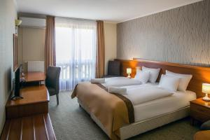 A bed or beds in a room at Hotel Narád & Park