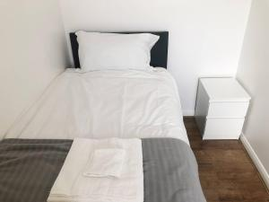 A bed or beds in a room at Modern Bright & Airy Guesthouse in North London
