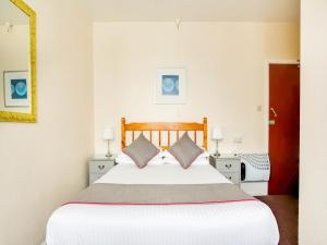 A bed or beds in a room at OYO Godolphin Arms Hotel