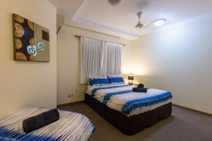A bed or beds in a room at 7 Waves - Airlie Beach
