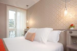 A bed or beds in a room at Hôtel Vic Eiffel