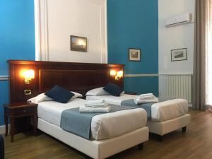 A bed or beds in a room at Napolit'amo Hotel Principe