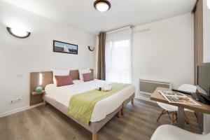 A bed or beds in a room at Appart'City Versailles Saint Cyr l'Ecole