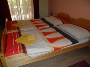 A bed or beds in a room at Napkorong Fogadó és Vendégház