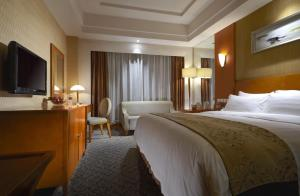 A bed or beds in a room at Dalian East Hotel
