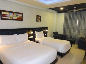 A bed or beds in a room at Pride Ananya Resorts