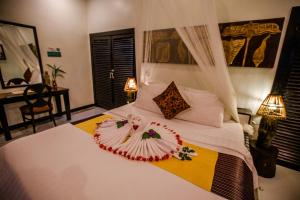 A bed or beds in a room at The Sanctuary Villa Battambang