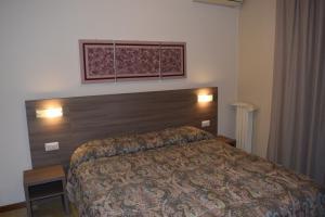 En eller flere senger på et rom på Hotel Pilotto