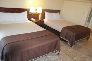 A bed or beds in a room at Shalimar Hotel of Las Vegas