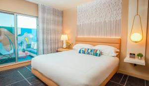 A bed or beds in a room at Kimpton Hotel Wilshire, an IHG hotel