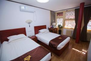 A bed or beds in a room at Beijing Jingyuan Courtyard Hotel