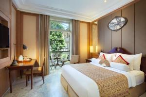 A bed or beds in a room at The Phoenix Hotel Yogyakarta - MGallery Collection