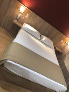 A bed or beds in a room at Hotel Victor Hugo