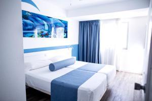 Een bed of bedden in een kamer bij Corralejo Surfing Colors Hotel&Apartments