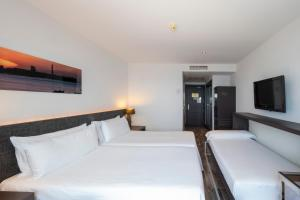 A bed or beds in a room at Tryp Cádiz La Caleta Hotel