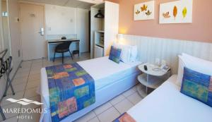 A bed or beds in a room at Maredomus Hotel