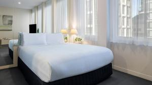 A bed or beds in a room at Oaks Melbourne on Collins Hotel