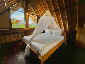 A bed or beds in a room at Flower Bud Bungalow Balangan
