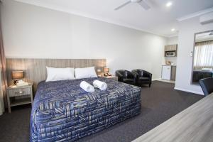 A bed or beds in a room at Harvest Lodge Motel - Gunnedah