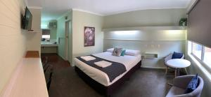 A bed or beds in a room at Finley Country Club Hotel Motel