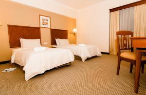 سرير أو أسرّة في غرفة في ذا زون أول سويتس ريزدنسز أون ذا بارك