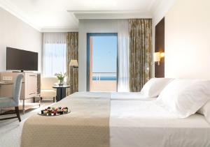 A bed or beds in a room at GPRO Valparaiso Palace & Spa