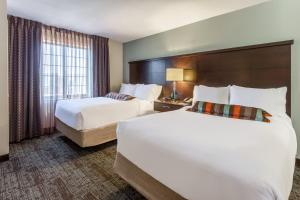 A bed or beds in a room at Staybridge Suites Davenport, an IHG hotel