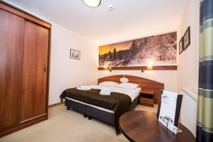 A bed or beds in a room at Nowa - Ski SPA Hotel