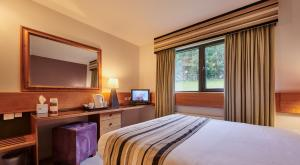 A bed or beds in a room at Stirling Court Hotel