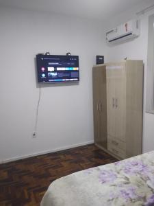 A television and/or entertainment centre at Quarto aconchegante no Calçadão