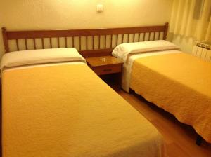 A bed or beds in a room at Pensión Lizaso