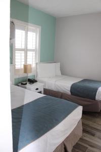 A bed or beds in a room at Shoreline Suites & Cabana Cottages – Beachfront