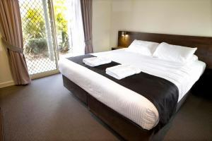 A bed or beds in a room at Mercure Bunbury Sanctuary Golf Resort