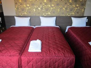 A bed or beds in a room at Hotel New Gaea Iizuka