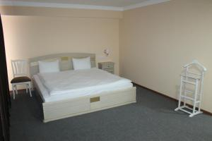 A bed or beds in a room at Tashkent Hotel