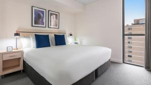 A bed or beds in a room at Oaks Brisbane Festival Suites