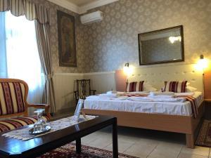 A bed or beds in a room at Festetich Kastélyszálló és Zsuzsanna Hotel
