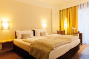 A bed or beds in a room at centrovital SPA & Sports Hotel