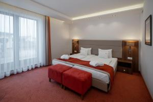 A bed or beds in a room at Bükkös Hotel & Spa