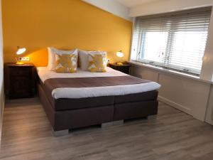 A bed or beds in a room at Strandhotel Om de Noord