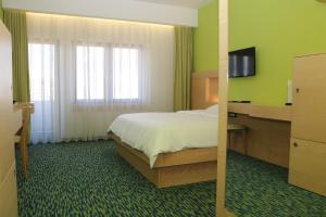 A bed or beds in a room at Hotel International Prishtina & Spa