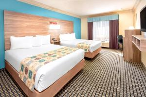 A bed or beds in a room at Ramada by Wyndham Houston Intercontinental Airport South