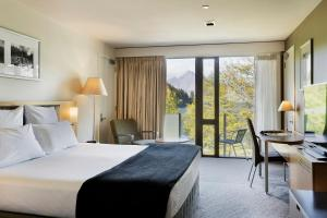 A bed or beds in a room at Novotel Queenstown Lakeside