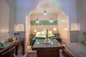 A bed or beds in a room at Riad El Walida