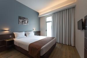 A bed or beds in a room at Moov Hotel Évora